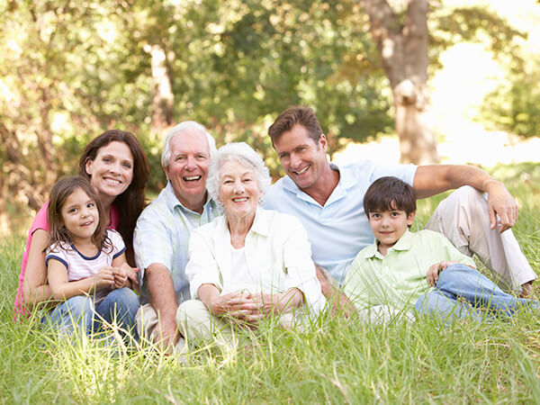 A family with two children, their parents, and two grandparents sitting on the grass in a park while smiling and hugging
