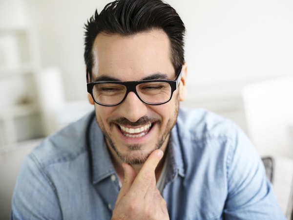 Man with dark hair and glasses laughing with his hand on his chin