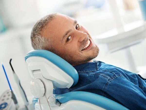 Man in a denim shirt reclining in one of our comfortable dental chairs