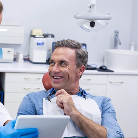 A man in a dental chair looking up at his family dentist with a hand on his chin