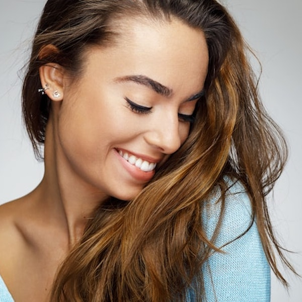 A woman with long brown hair looking down smiling