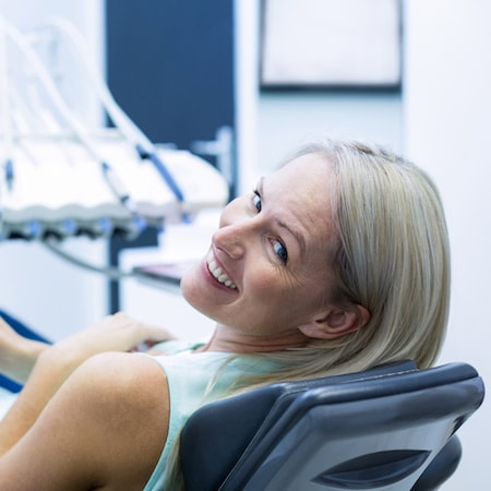 Woman laying on a dental treatment chair as she waits to receive a root canal
