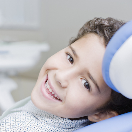 Young boy laying a in dental chair and looking back at his dentist while smiling