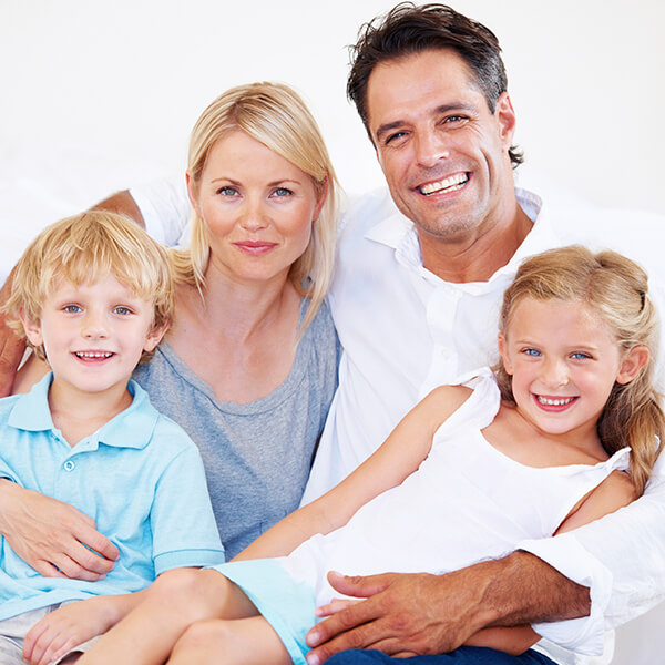 A family of four smiling while they are sitting on a sofa and enjoying the Cottage Lake Family Dentistry difference