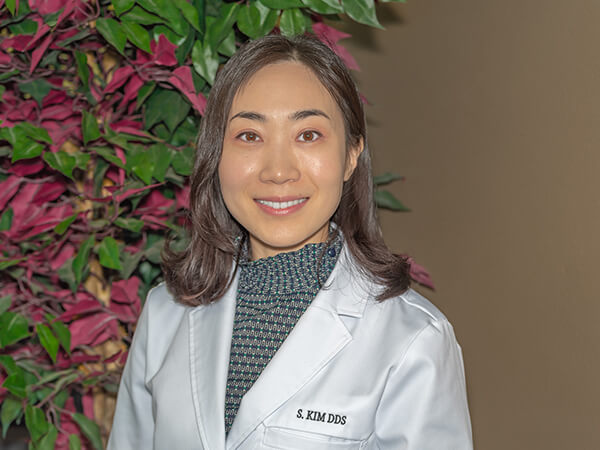 One of our lead Cottage Lake dentists, Dr. Kim wearing scrubs in front of a tree
