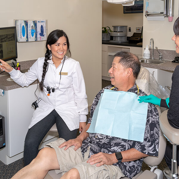 Our dentist explaining a dental treatment to her male patient in a dental chair