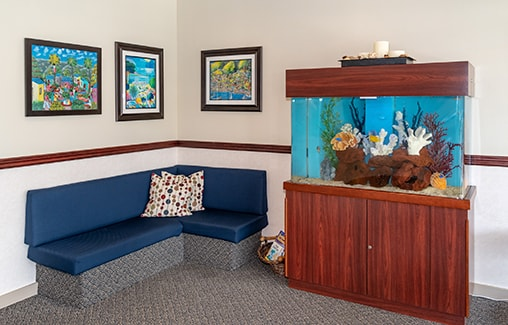 The waiting room of the dental office showing a sofa and a fish tank