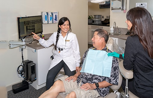 One of our specialists and a dental assistant talking to a man who is sitting in the dentist's chair smiling