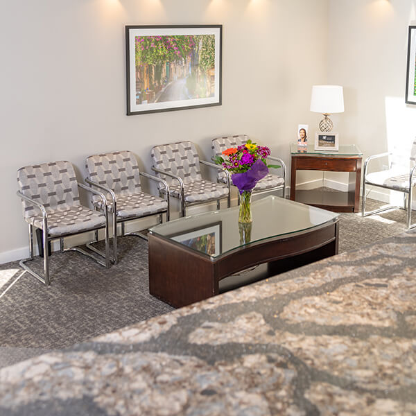 An inside look at our waiting room with 4 comfortable chairs and a coffee table